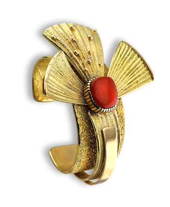 A gold and red coral cuff made by Michael Roanhorse Native American Jewelry.