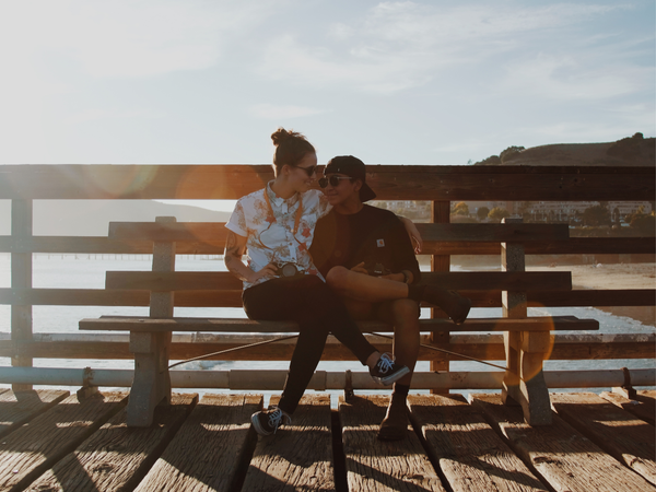 two women sitting on a bench on a california pier looking at each other in because they are in love