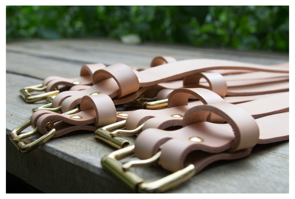 Veg tanned leather belts on a table outside