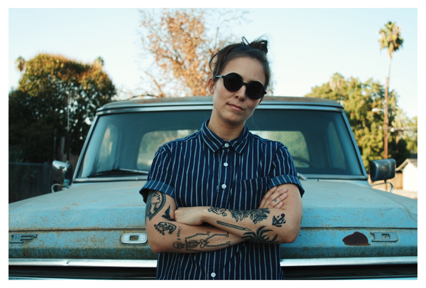 Woman with tattoos and sunglasses standing with arms crossed in front of old Ford
