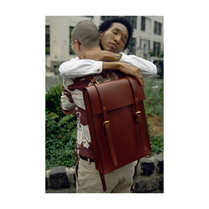 Two People Hugging While One Person is Wearing Brown Backpack