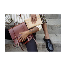 Two People Sit on Stairs Holding Leather Clutch and Small Leather Backpack; We Can Only See Their Hands