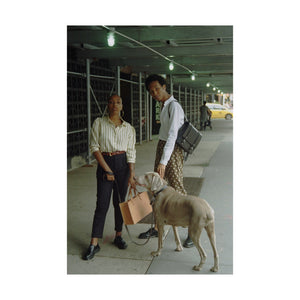 Two People Standing with Dog, One Person Has Tan Tote and Other Person Has Small Black Backpack