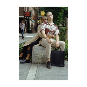 One Person Hugs Second Person While They Sit On Large Rock, Second Person Has Black Tote Between Legs