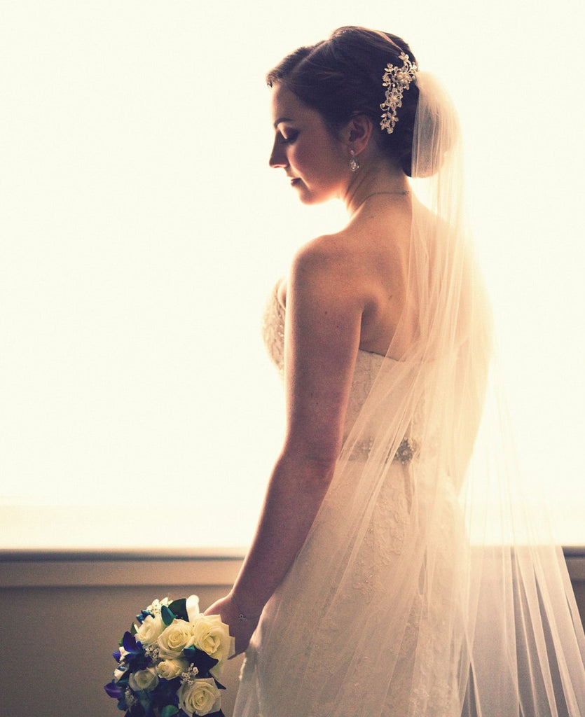 bun updo with asymmetrical hair comb and wedding veil