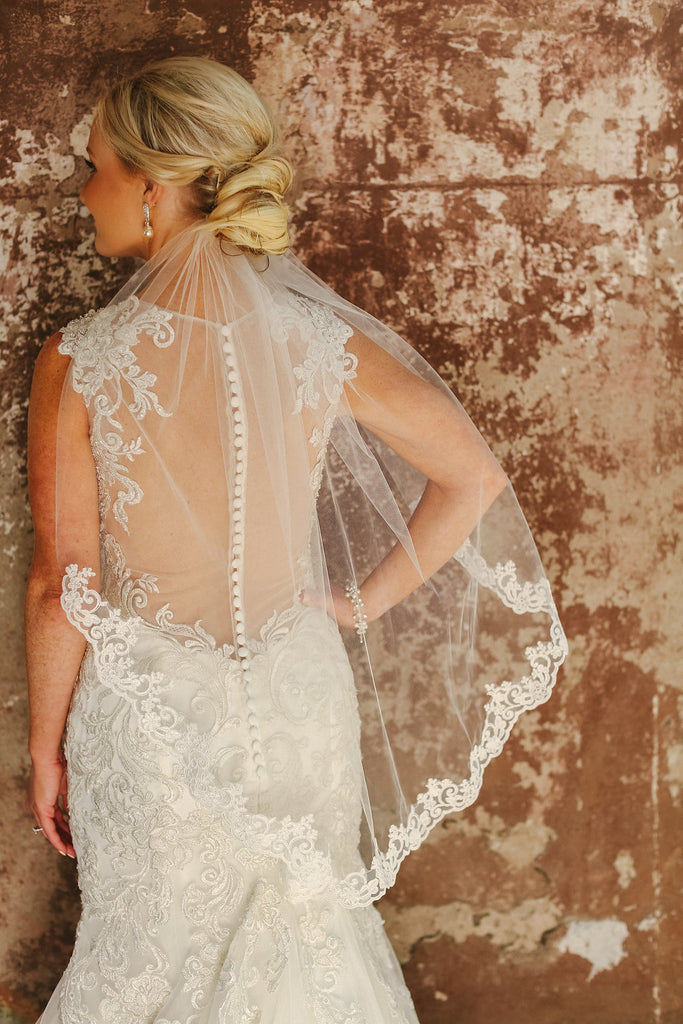 short elbow length veil with lace trim under brides low updo hairstyle