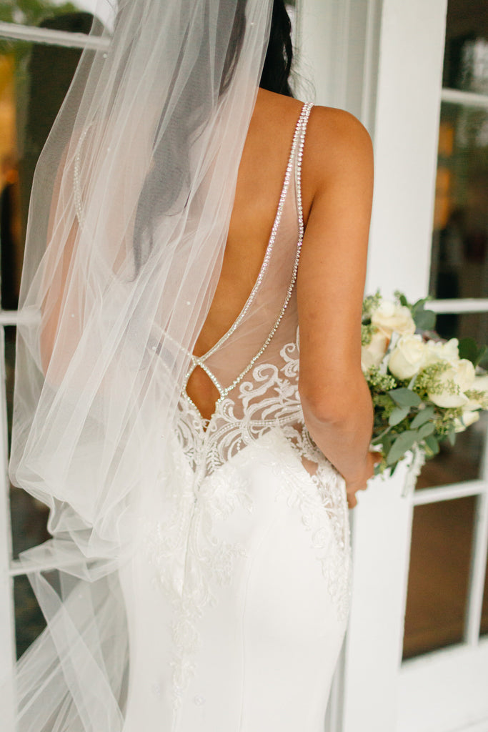 long veil with scattered rhinestone on bride with low back dress