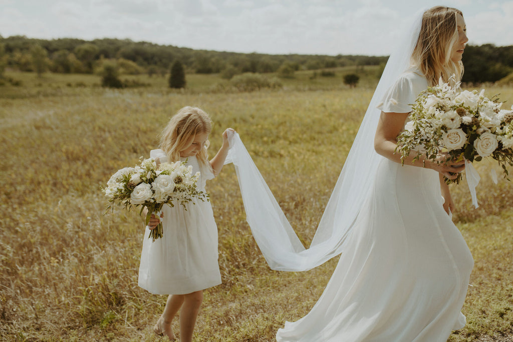 elopement in wheat fields with flower girl holding bridal veil