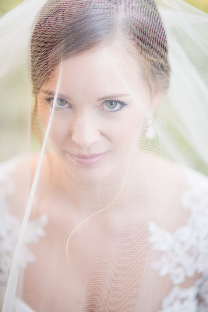 drop wedding veil over face with bride in lace gown
