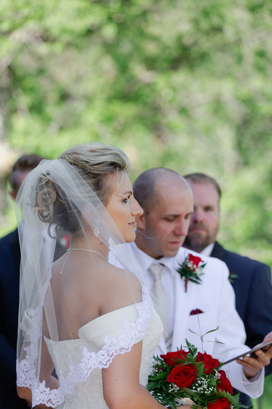 winter bride in elbow length french lace veil over updo