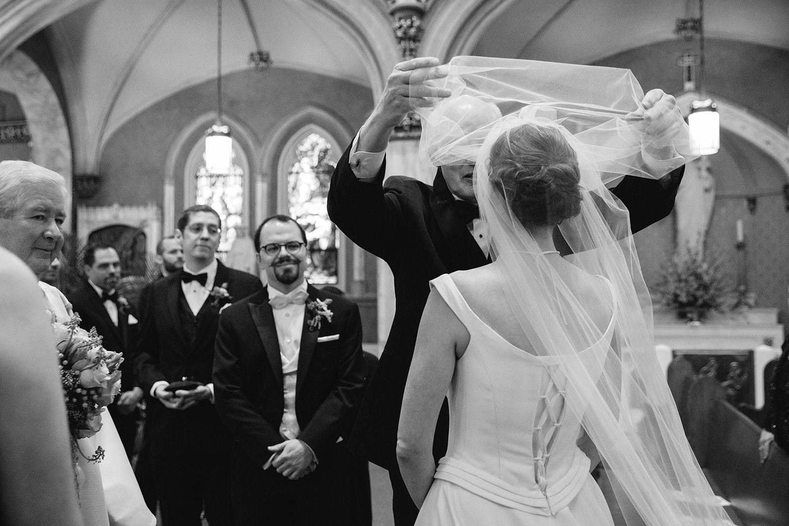 Dad lifting blusher veil over bride's face