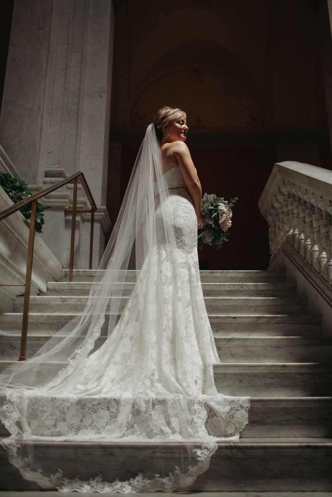 bride on staircase in light ivory cathedral wedding veil with trim