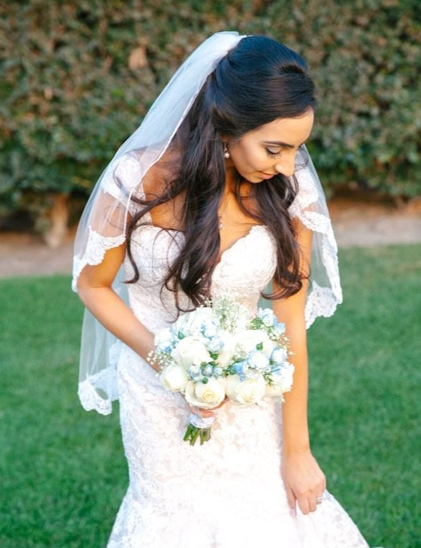 elegant bride with lace fingertip length wedding veil in half up hairstyle