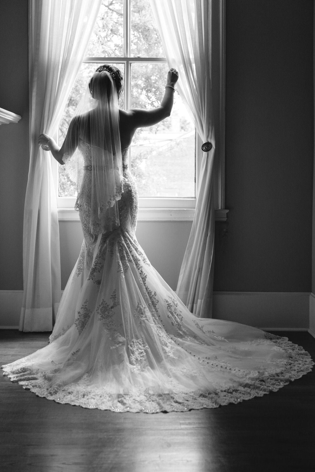 bride in one tier veil looking out window