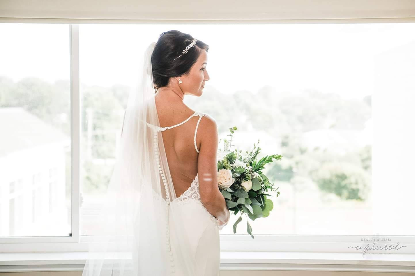Bride with Low Back Dress, Sheer Wedding Veil, and White Bouquet