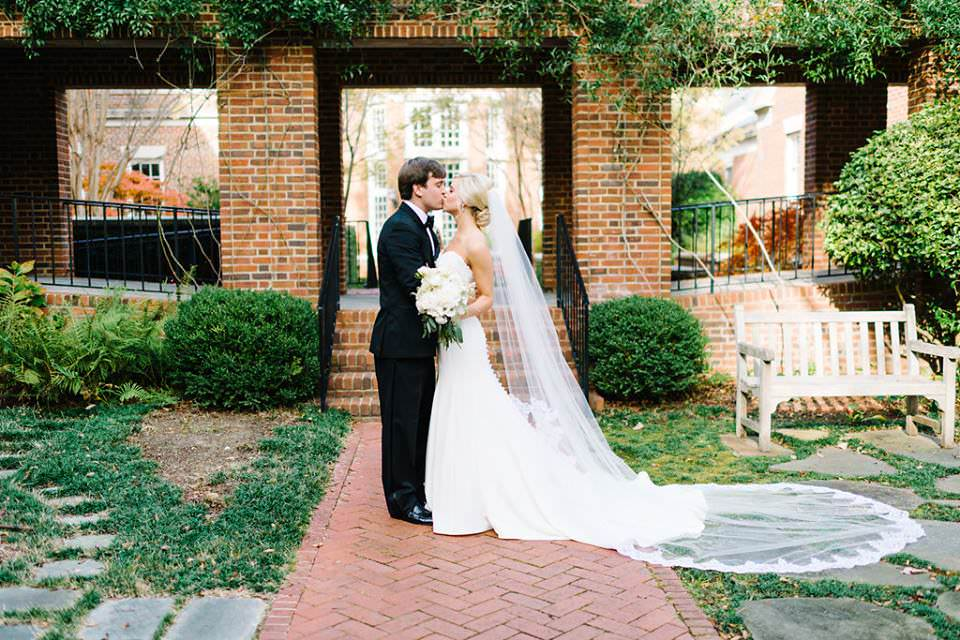 garden wedding with bride in strapless white dress and cathedral lace veil