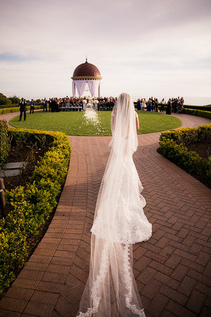 Bride walking down the aisle with long lace cathedral veil in ivory