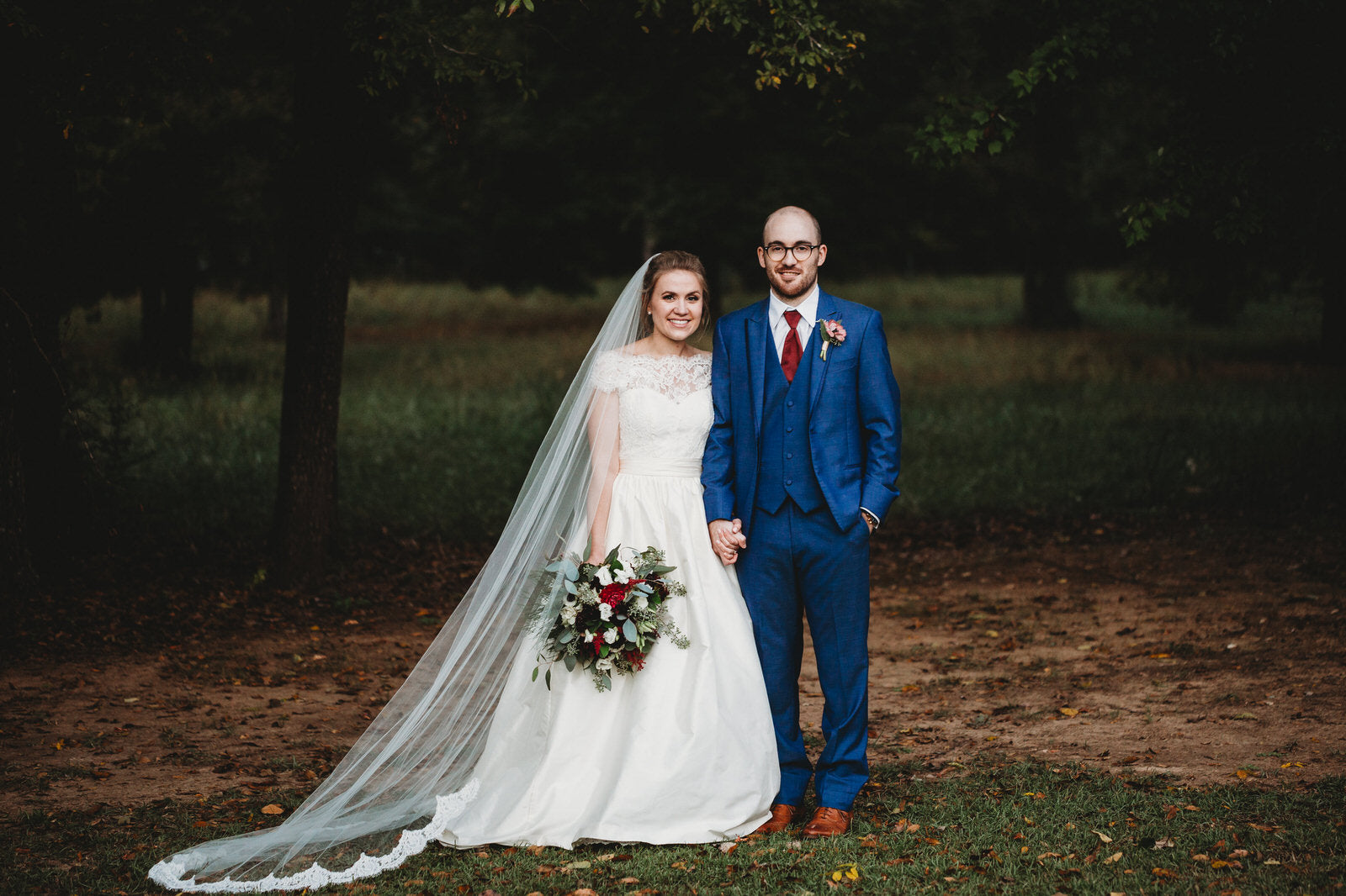 outdoor wedding with bride in long cathedral veil trimmed in alencon lace