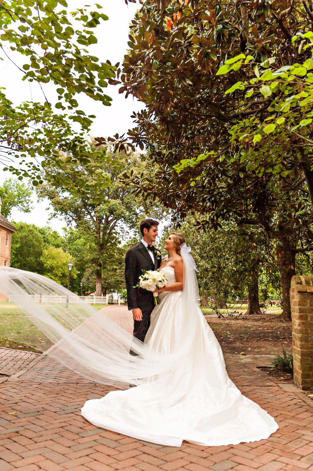 formal wedding portrait with bride in long cathedral veil and silk ballgown