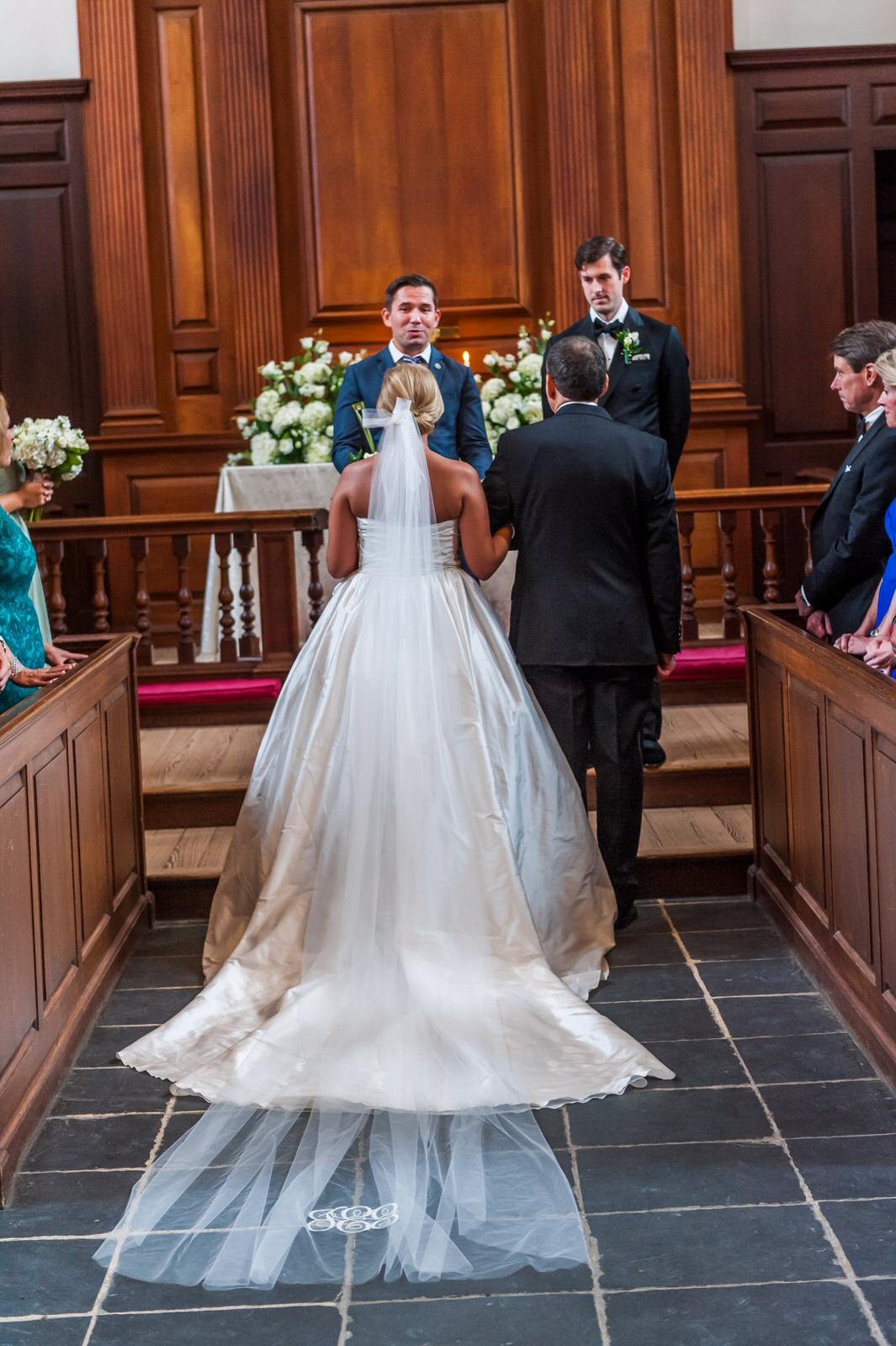 bride walking down church aisle in monogrammed cathedral veil