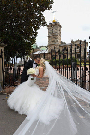 bride and groom with long cathedral length crystal wedding veil