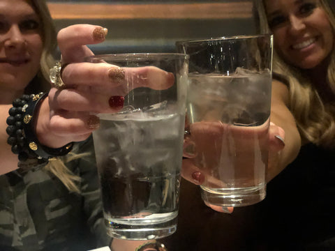 Two friends saying cheers with water
