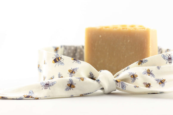 a bar of honey soap with a white head band with bee design