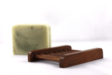 a bar of peppermint soap with a dark wooden soap dish