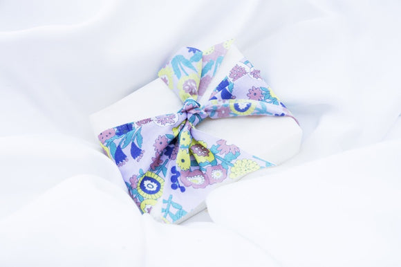 a wedding favour soap wrapped in a blue floral ribbon