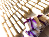 rows of soaps with two soaps wrapped in lace ribbon and purple ribbon