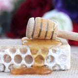 honey soap covered with liquid honey with a honey stirrer on top