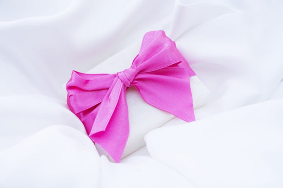 a wedding favour soap wrapped with pink ribbon