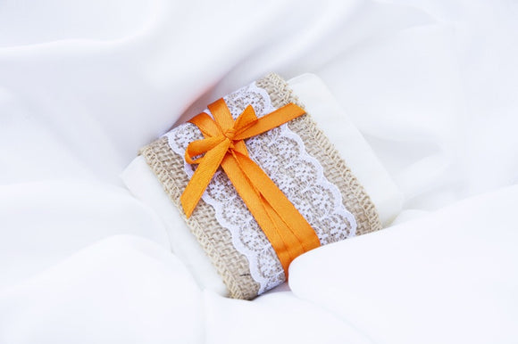 a bar of wedding favour soap wrapped with lace ribbon and orange ribbon