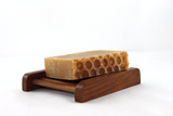 a bar of honey soap on a dark wooden soap dish