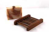 a bar of walnut soap on a dark wooden soap dish