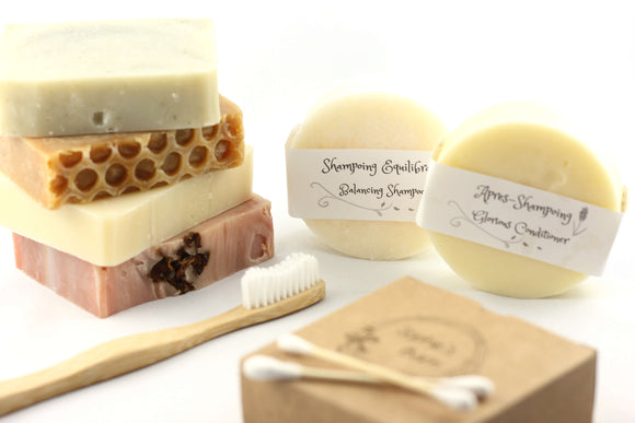 a bar of peppermint soap, a bar of honey soap, a bar of olive oil soap and a bar of argan oil and rosehip soap next to a solid shampoo, a solid conditioner, a bamboo toothbrush and a box of bamboo cotton buds