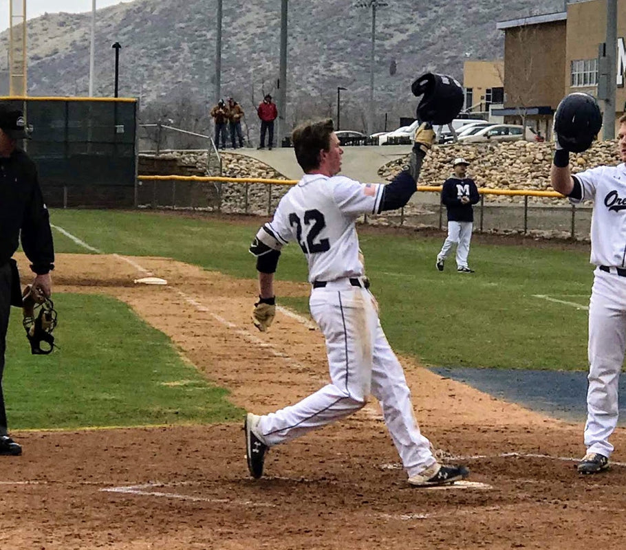 Picture of Gabe Garvins hitting a dinger wearing BRUCE BOLT 100% Cabretta Leather Premium Pro Natural Series Batting Gloves.  Natural Tan Leather with Navy Trim and Navy Lightning Bolt. The Best Batting Gloves.
