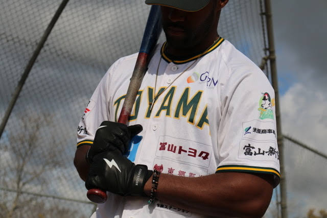 Picture of Kevin Maxey American Outfielder of the Toyama Thunderbirds wearing a pair of BRUCE BOLT 100% Cabretta Leather Short Cuff Original Series Premium Pro  Black Leather with White Lightning Bolt.  The Best Batting Gloves.