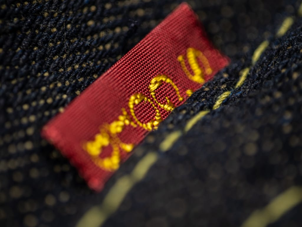 The Strike Gold 2109 Brown Weft Jeans red tag