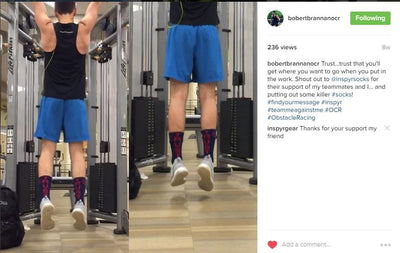 male-doing-a-pull-up-with-blue-shorts-black-top-trust-socks