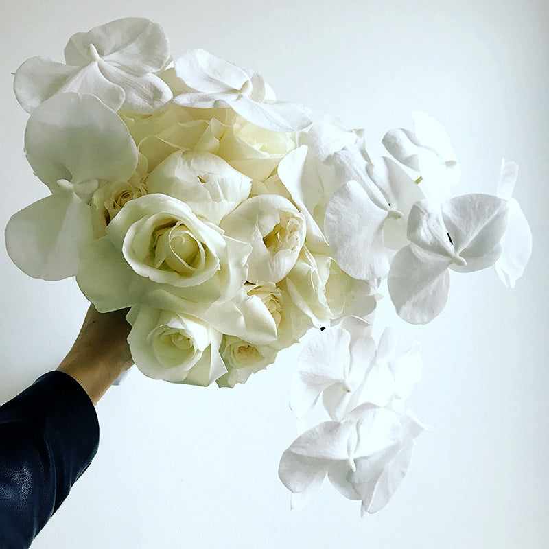 White bridal bouquet wedding flowers being held by hand