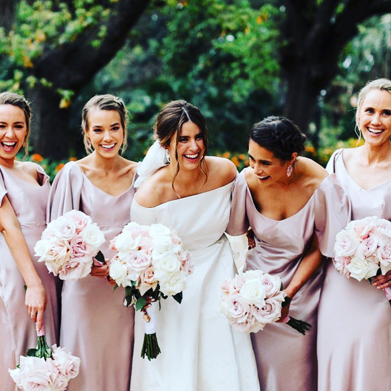 Bride and bridesmaids laughing and holding wedding bouquets flowers