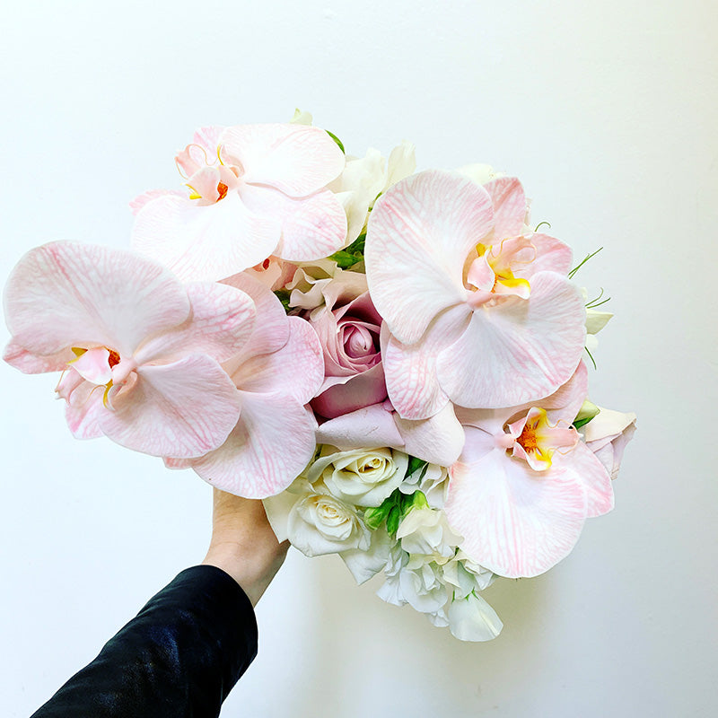 Bridal bouquet in pink tones being held by had