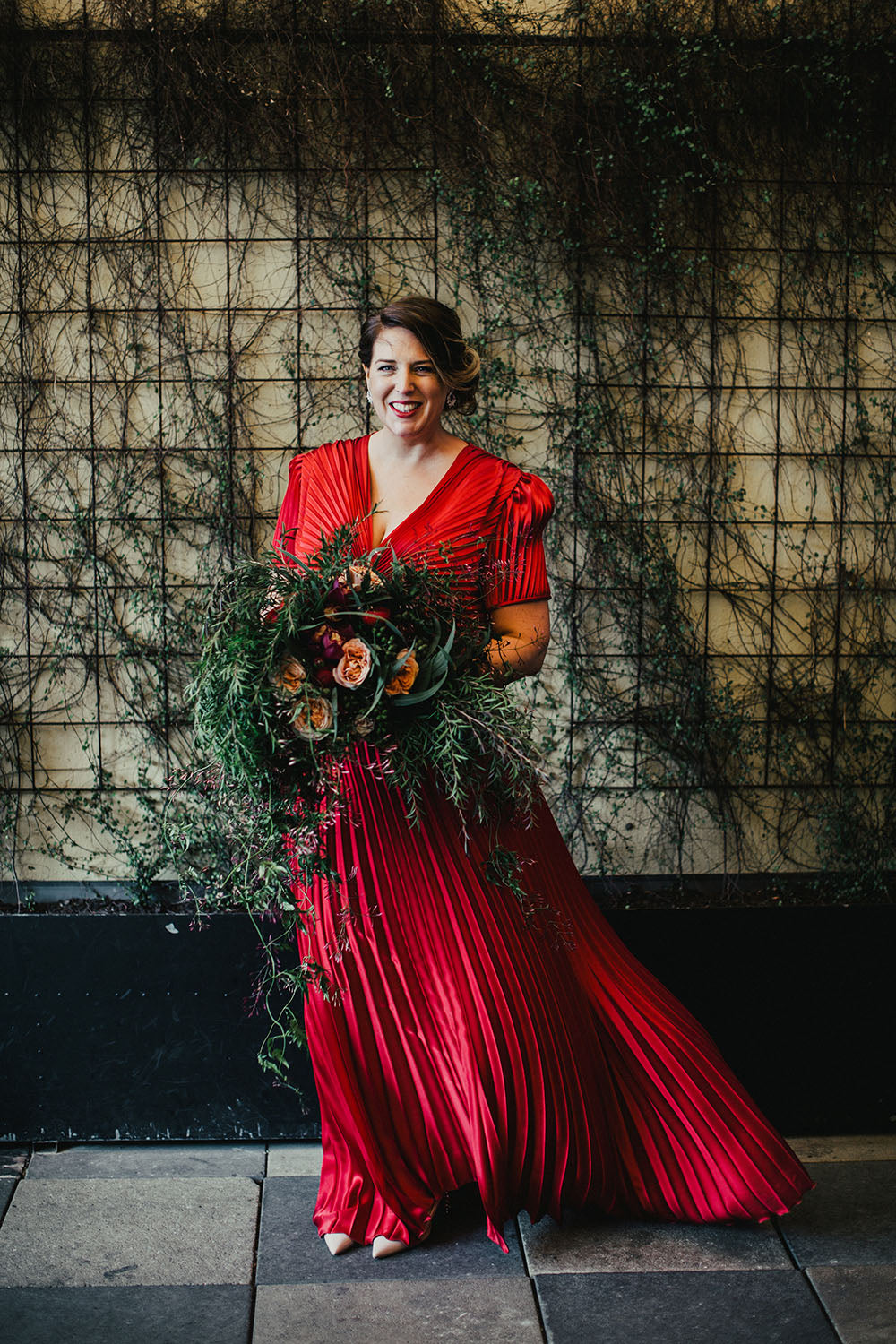 Bride holding bridal bouquet at wedding in red dress