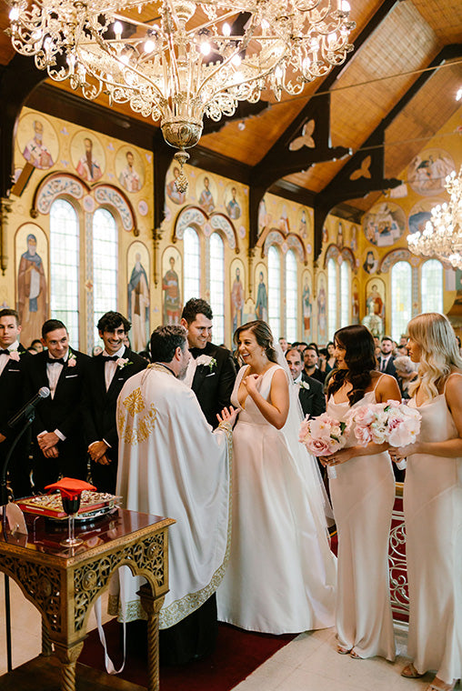 Bridal party at alter with priest