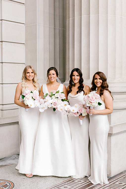 Bridesmaids standing together holding bridal bouquets