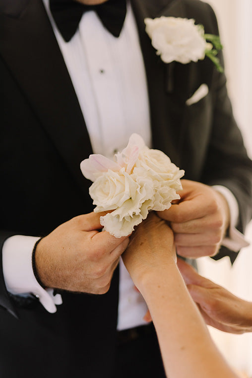 Groom fitting wedding flowers corsage to female's arm