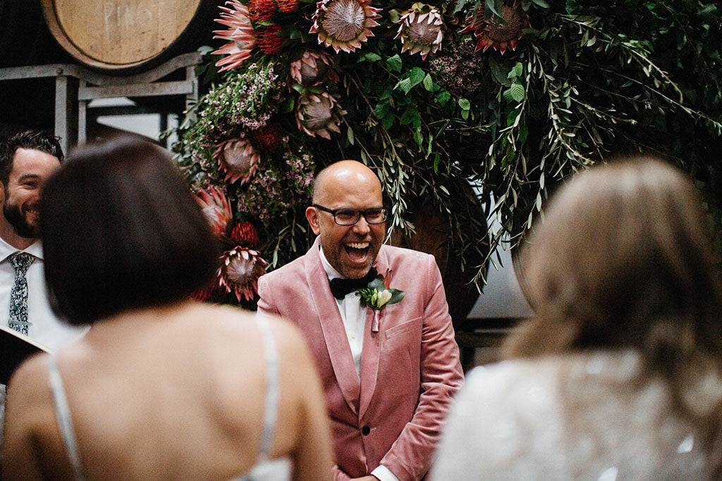 Groom standing in front of Wedding Flowers