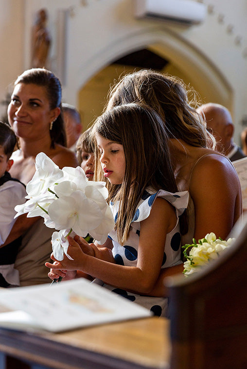 Wedding flowers at ceremony held by flower girl