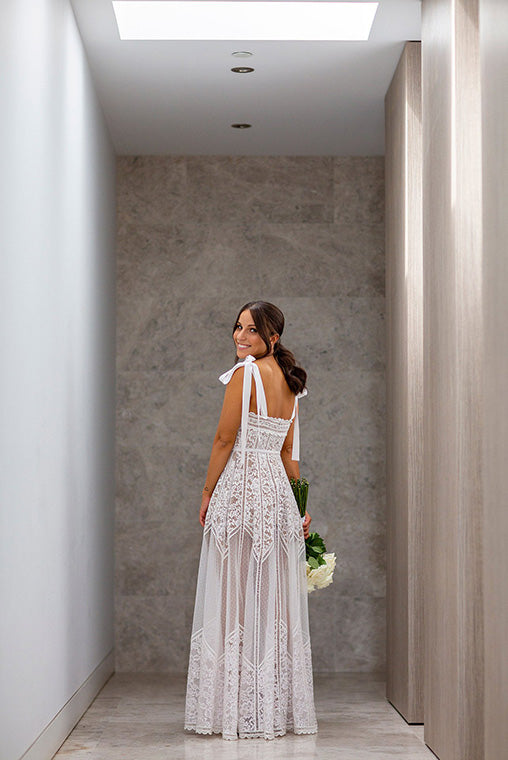Bride in white gown holding wedding flowers